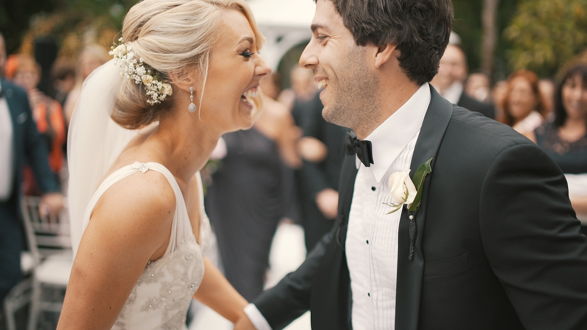 a bride and groom looking at each other and laughing